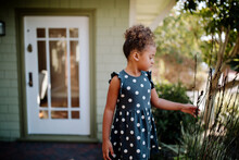 Young Girl On Porch Of House Touching Plants