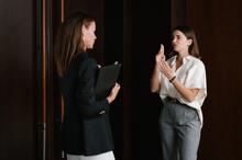 Deaf Businesswomen Using Sign Language In Hallway
