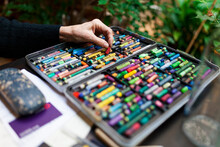 Artist Hand Picking A Crayon From Crayon Case