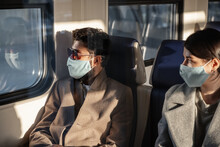 Male And Female Passengers In Masks Looking Out Train Window