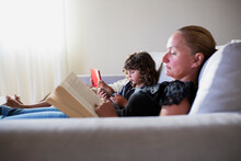 Young Mother Reading A Book While Her Kids Using A Digital Tablet
