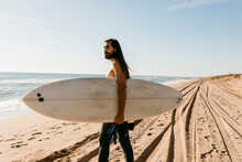 Men With Surfboard At The Beach