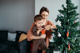Loving mom and son decorating tree.