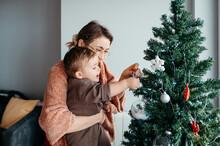 Mom With Baby Decorating Xmas Tree.