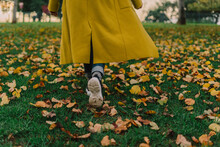 Detail Of Senior Woman From Back Walking At Park With Yellow Coat In Autumn