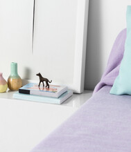 Minimalistic Bedside Table With Books, A Dog Figurine, Two Vases And A Framed Picture Next To A Bed