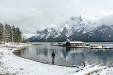 Person Standing By Lake With View Of Snowy Mountains