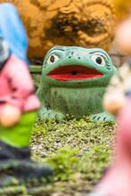 Garden With Frog Sculpture. Green Ceramic Figure. Selective Focus.
