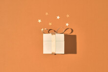 Golden Gift Or Present Box And Stars Confetti On Color Table Top View. Flat Lay Composition For Birthday, Christmas Or Wedding.
