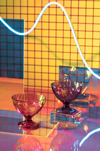 Two Glasses Stand On Glass With Neon Line