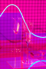 Glasses Of Champagne On A Pink Mosaic Background With The Effect Of Drawing Blue Light On A Long Shutter Speed