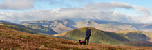 Walker And His Dogs On High Raise At Sunrise. Lake District, Cumbria, UK.