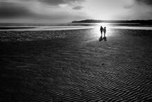 Silhouette Of Siblings On Rippling Sandy Beach