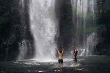 Tourists Looking At Waterfall In Jungle