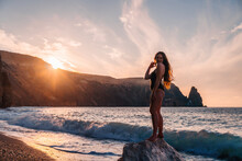 Selective Focus. Happy Carefree Sensual Woman With Long Hair In Black Swimwear Posing At Sunset Beach. Silhouette Of Young Beautiful Playful Positive Woman Outdoor. Summer Vacation And Trip Concept
