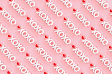 """XOXO - Hugs And Kisses Abbreviation- 3D Render Of The Word """"XOXO"""" On A Pink Background With Red Hearts"""