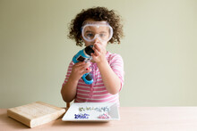 Girl In Safety Glasses With Blue Screwdriver