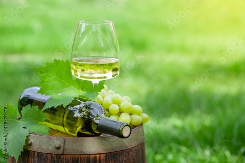 Fotografia Wine bottle, glass and grape on old wine barrel