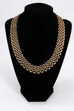 A Gold Chain On A Black Bust Isolated On White Background
