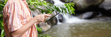 Bearded Botanist Wearing Panama Hat Using Digital Tablet Pointing At Blank Screen With Happy Expression, Standing At Mountain River Against Waterfall Background While Conducting Water Analysis