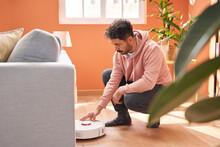 Man Pushing Button On Robotic Vacuum Cleaner