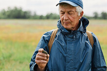 Middle Aged Male Wearing Blue Jacket Holding Old Coin Found In Meadow, Looking Attentively At His Finding, Numismatist Posing Outdoors With Historical Artifact.