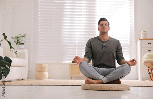 Murais de parede Man meditating on wicker mat at home. Space for text