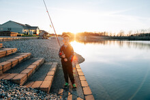 Boy Standing At Pond's Edge With A Fishing Rod.