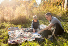 Father And Son Sit On Quilt Looking At Notebook