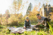 Father And Son Sit On Quilt In Grass