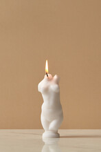 Candle With Female Shape On Brown Background