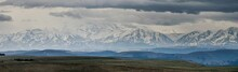 Panoramic Landscape View Over Gum-bashi Mountain Pass, With New Green And Old Brown Grass On Cliffs, Dark Clouds Before The Storm, Сaucasus Mountian Range And Elbrus Mountain. Karachay-Cherkessia