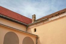 The Rooftop With Red Tiles On A Old Eropean Building With Chimneys