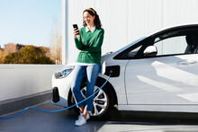 Woman Using Smartphone Near Electric Car On Charging Station