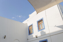 A White Building With Blue Window Frames Against A Blue Sky In The Greek Style. Travel And Architecture Concept. Bodrum, Turkey