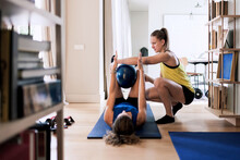 Trainer Helping Woman To Do Exercise With Ball