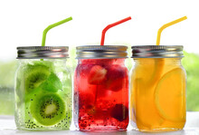 Bright Colorful Refreshing Summer Drinks In Glass Jars With Lid And Straws On A White Background