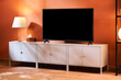 TV set and lamp on cupboards at home