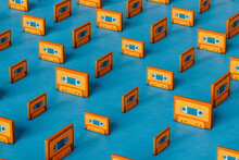 Orange Musicassette On Blue Background Arranged In Different Positions And Sizes
