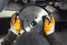 Closeup Male Tehnician Mechanic Greasy Hands In Gloves Install New Car Oem Brake Steel Rotor Disk During Service At Automotive Workshop Auto Center. Vehicle Safety Checkup And Maintenance Concpet