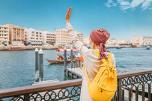 Woman Tourist Passenger Waits For A Ferry Boat On The Other Side Of The Dubai Creek Canal Wearing A Medical Mask To Prevent Covid-19 Infection