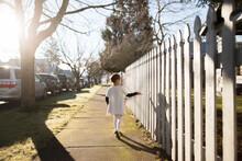 Girl Walks Along White Picket Fence