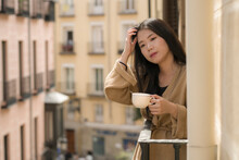 Young Contemplative And Beautiful Asian Woman At Home Or Hotel Balcony - Thoughtful Chinese Girl Having Morning Coffee Enjoying Street View Thinking Relaxed