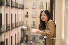 Young Contemplative And Beautiful Asian Woman At Home Or Hotel Balcony - Thoughtful Japanese Girl Having Morning Coffee Enjoying Street View Thinking Relaxed