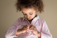 Focused Girl Fastens Tiny Shirt Buttons
