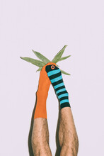 A Man Dressed In Various Colorful Socks Holds A String Bean