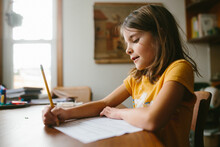 Close-up Of Girl Sitting At Table At Home Writing On Paper With Pencil