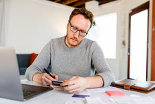 Man With Glasses Calculates Annual Expenses For His Work From Home Startup