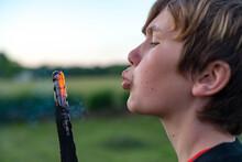 Boy Blowing Embers
