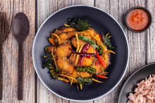Flat Lay Spice Stir-fried Snakehead Fish With Herbs And Vegetables Like Fingerroot, Green Peppercorns, Kaffir Lime Leaves And Holy Basil Leaves, A Healthy Thai Food Dish Called Pad Cha Pla Chon.